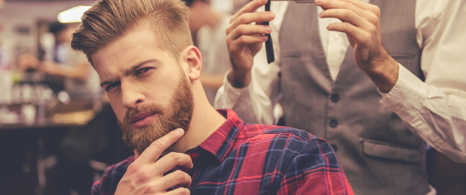 A handsome man in a barbershop touching his beard for the page booking software for the barbershop.